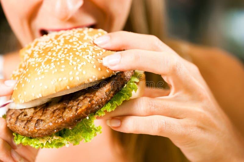 Mulher em um restaurante que come o Hamburger fotos de stock