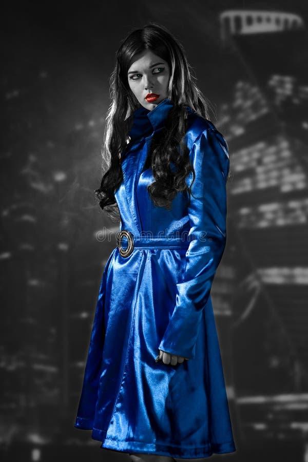 Mulher em um revestimento azul com os bordos vermelhos preto e branco na cidade o imagem de stock royalty free