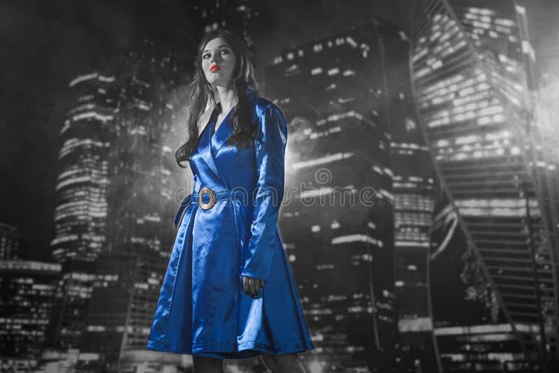 Mulher em um revestimento azul com os bordos vermelhos preto e branco na cidade o imagens de stock