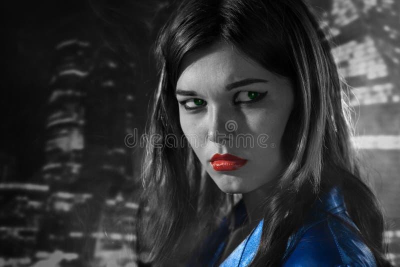 Mulher em um revestimento azul com os bordos vermelhos preto e branco na cidade o foto de stock