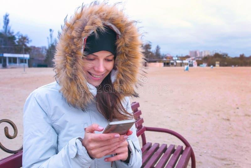 Mulher em um revestimento branco da pena que senta-se em um banco na praia e que olha o vídeo de surpresa no telefone celular imagem de stock royalty free