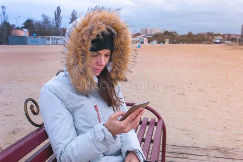 Mulher em um revestimento branco da pena que senta-se em um banco na praia e que olha o vídeo triste no telefone celular fotografia de stock royalty free
