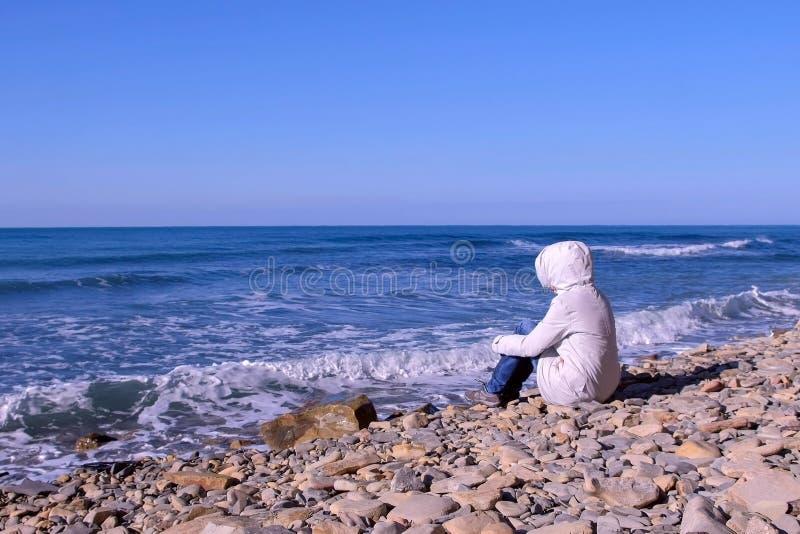 A mulher em um revestimento e em uma capa brancos da pena senta-se na costa e nos olhares nas ondas tormentosos do mar que batem  imagem de stock