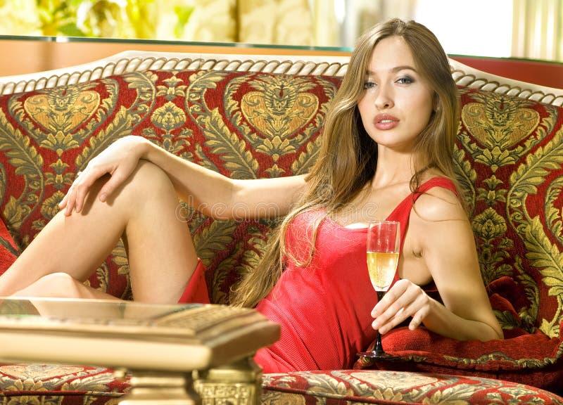Mulher em um sofá com vidro do vinho imagens de stock