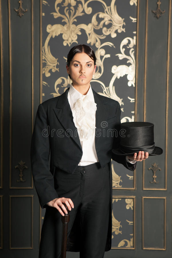 Mulher em um traje clássico dos homens que guardara um cilindro fotografia de stock