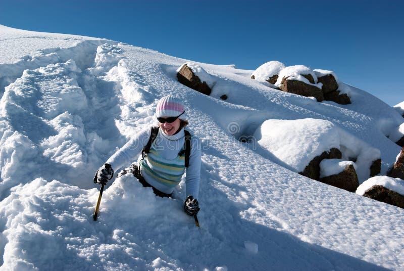 Mulher em um trajeto da neve nas montanhas fotos de stock royalty free