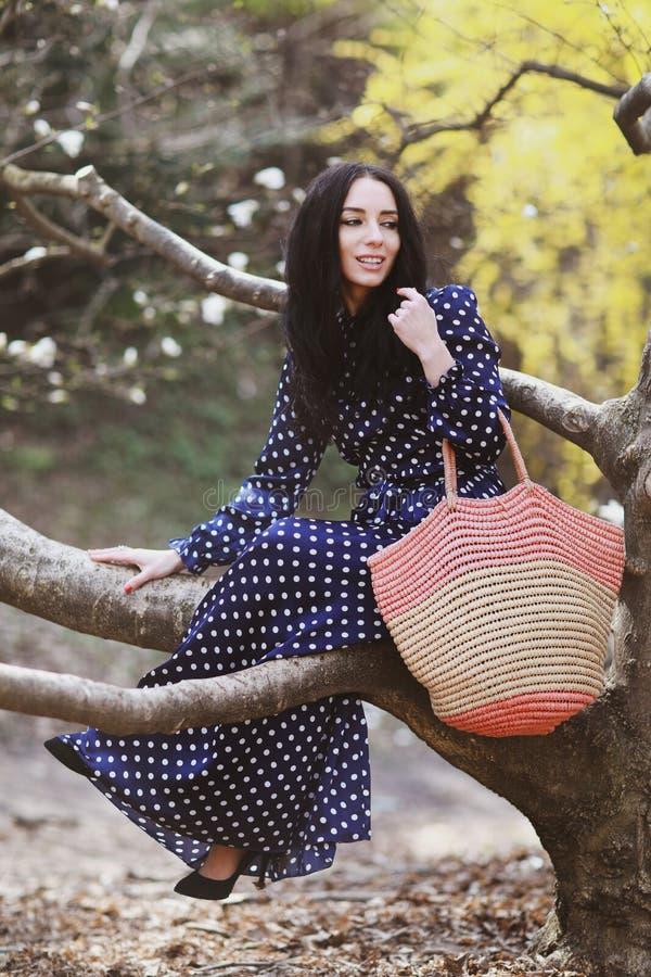 Mulher em um vestido azul e um saco feito malha perto da florescência da magnólia imagem de stock royalty free