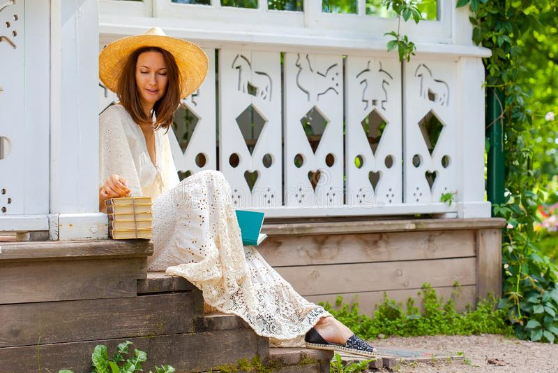 Mulher em um vestido branco e em um chapéu com livros imagem de stock royalty free