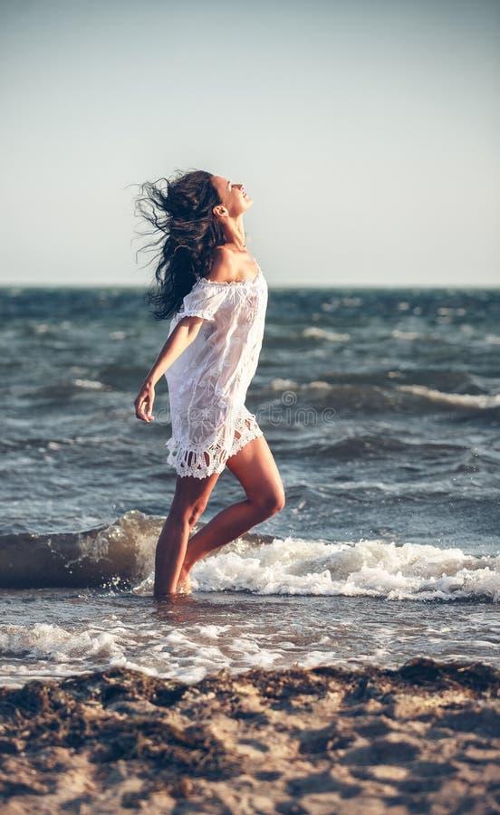 Mulher em um vestido branco na praia foto de stock