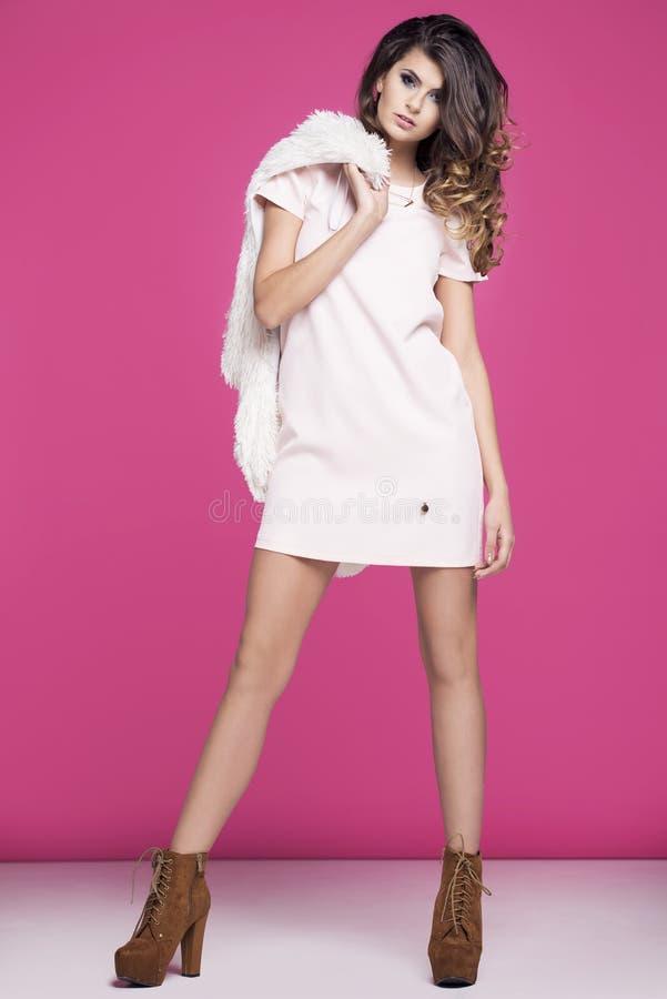 Mulher em um vestido cor-de-rosa que está em um fundo cor-de-rosa imagem de stock royalty free
