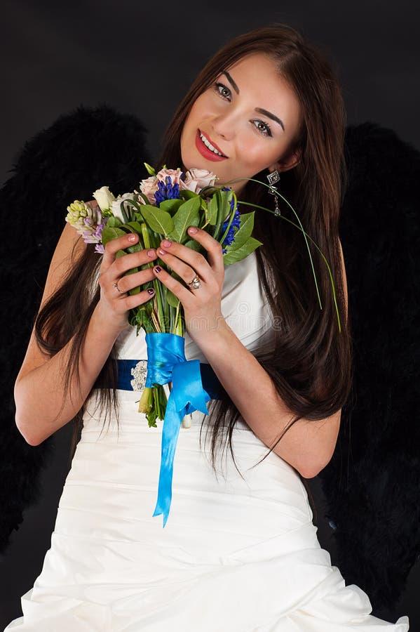 Mulher em um vestido de casamento com asas pretas fotos de stock royalty free