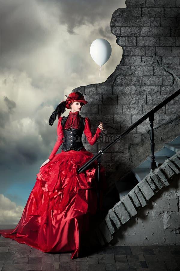 A mulher em um vestido histórico vermelho está guardando uma bola branca do ar imagens de stock