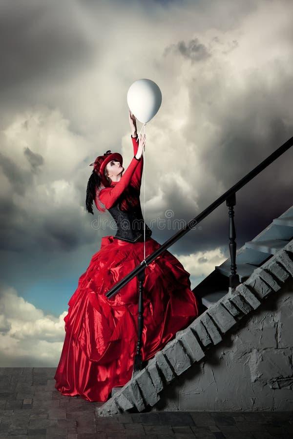 A mulher em um vestido histórico vermelho está travando um balão branco imagens de stock royalty free