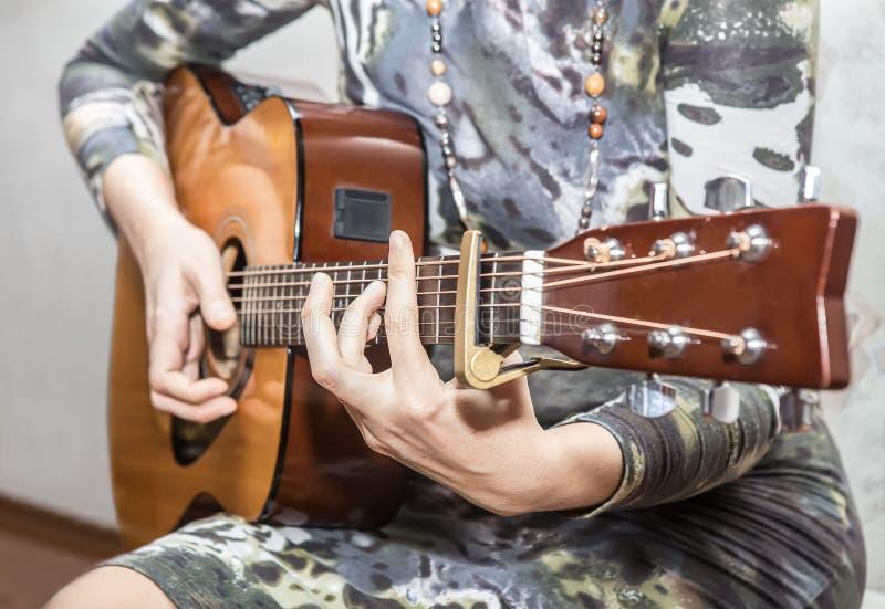A mulher em um vestido joga uma guitarra acústica fotos de stock royalty free