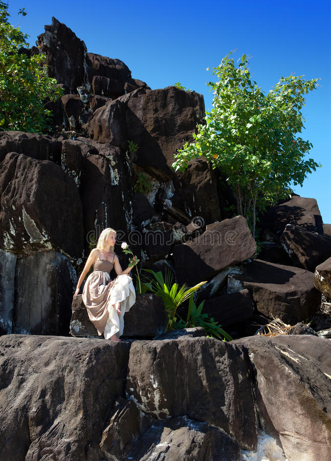 mulher em um vestido longo em pedras pretas polynesia imagem de stock