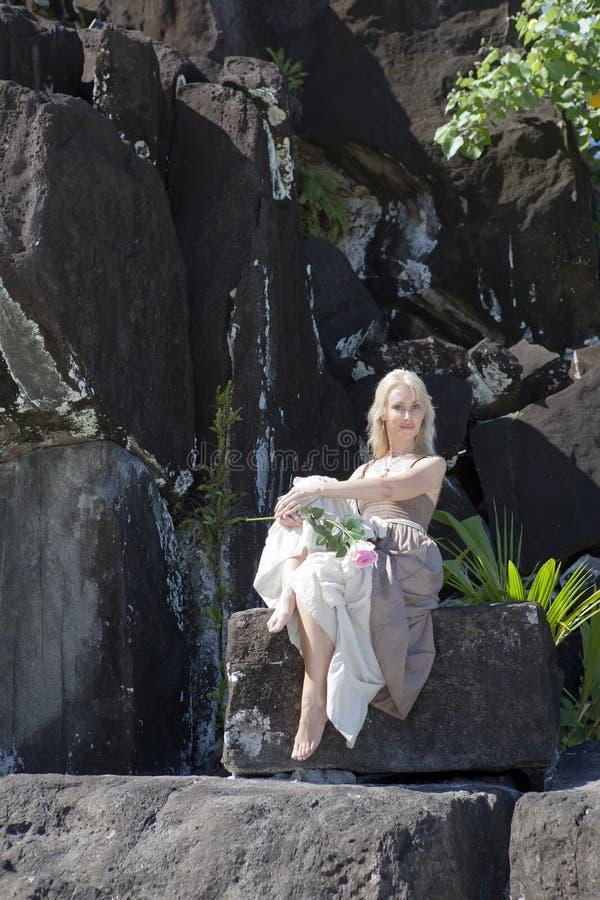 mulher em um vestido longo em pedras pretas polynesia imagem de stock royalty free