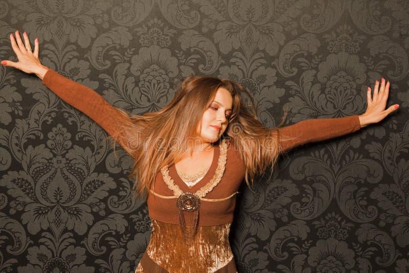 Mulher em um vestido marrom que está ao lado de uma parede imagens de stock royalty free