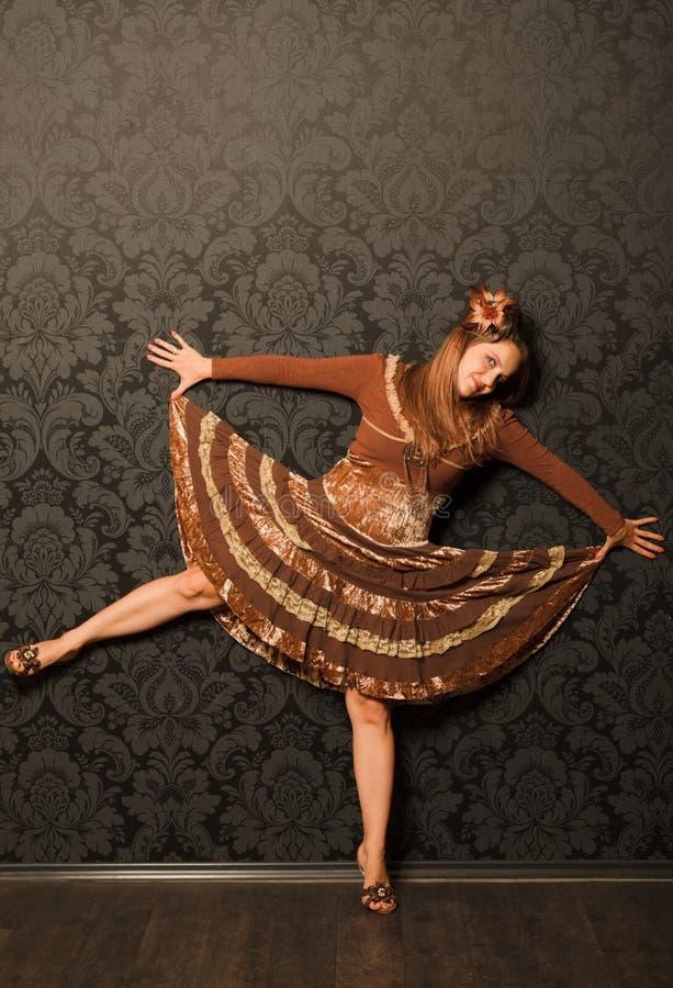 Mulher em um vestido marrom que está ao lado de uma parede imagem de stock royalty free