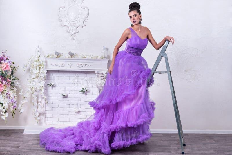 Mulher em um vestido na escada portátil imagens de stock royalty free