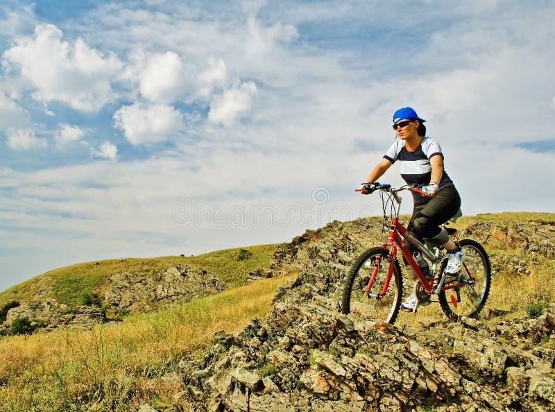 Mulher em uma bicicleta imagem de stock