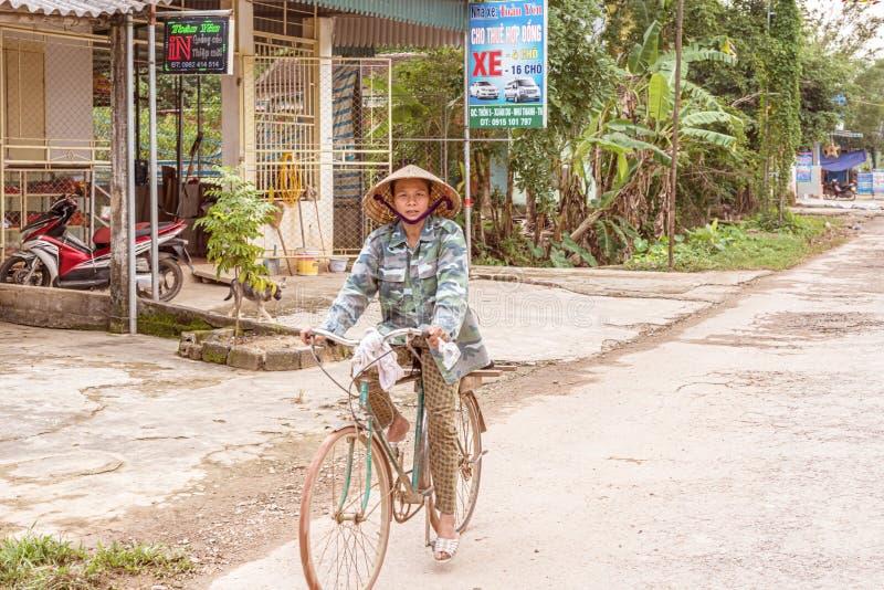 Mulher em uma bicicleta na vila pequena Xuan Minh em Vietname fotos de stock royalty free