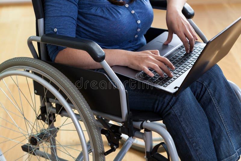 Mulher em uma cadeira de rodas com portátil fotografia de stock
