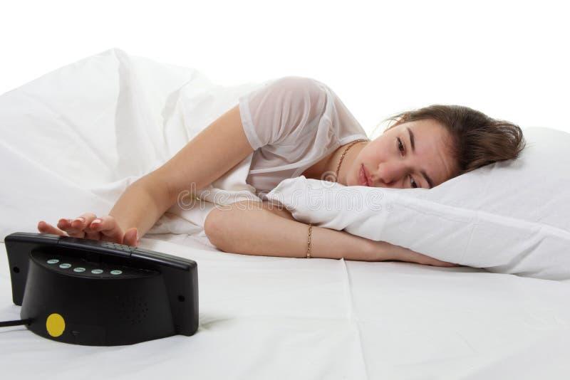 Mulher em uma cama com despertador imagem de stock