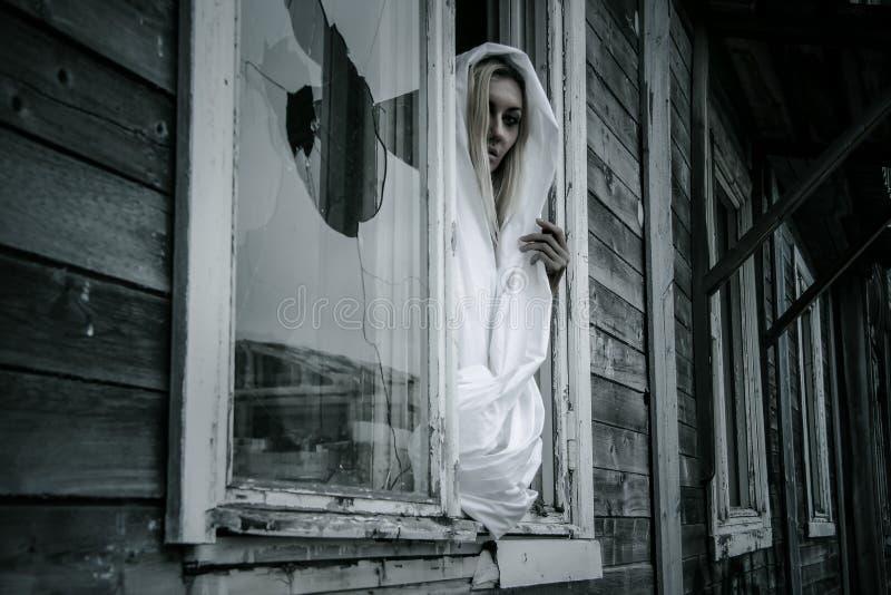 Mulher em uma camisa branca perto da janela fotos de stock royalty free