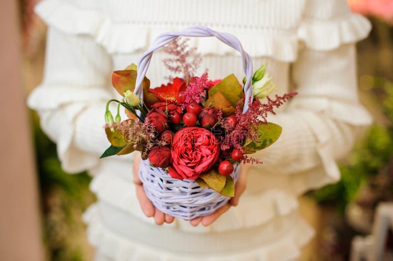 Mulher em uma camiseta branca que guarda uma cesta de vime bonito com composição da flor do Valentim imagens de stock royalty free