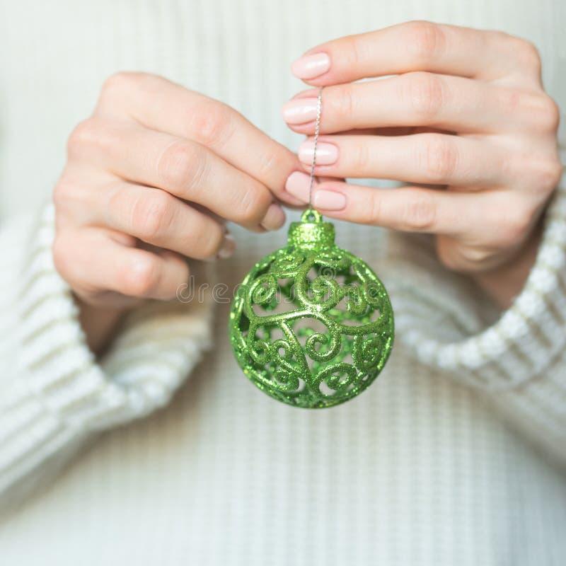 Mulher em uma camiseta de lã morna leve que guarda bolas em suas mãos, espaço de um verde do brinquedo da cópia, foco seletivo Na fotos de stock