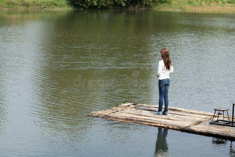 Mulher em uma jangada de bambu no rio foto de stock