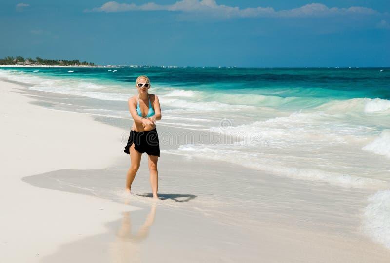 Mulher em uma praia branca da areia fotografia de stock