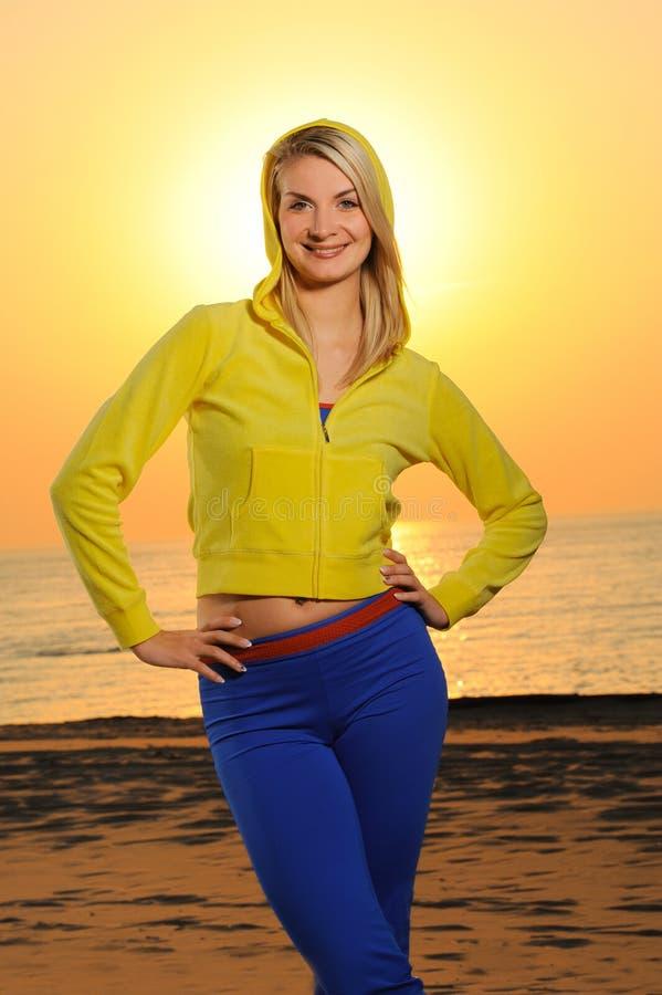 Mulher em uma praia no por do sol foto de stock royalty free