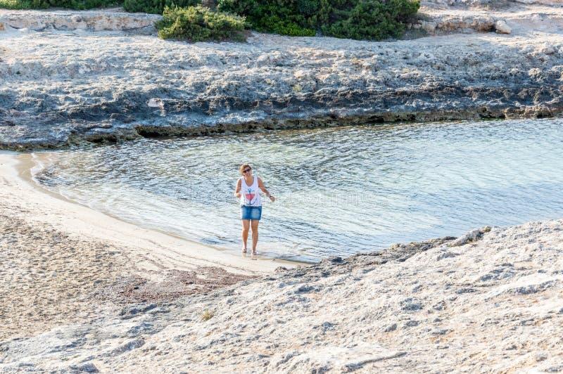 Mulher em uma praia no seacoast de Ostuni foto de stock