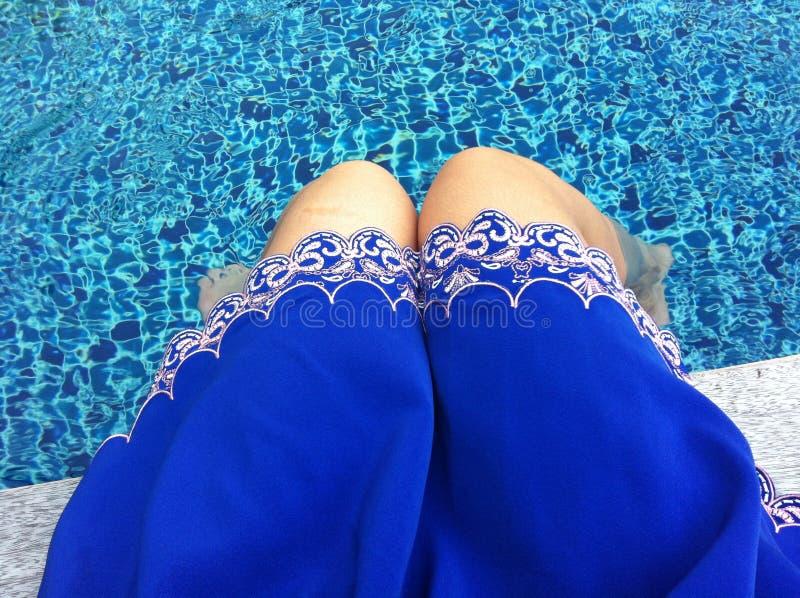 Mulher em uma saia azul que senta-se ao lado da associação com água clara fotos de stock royalty free