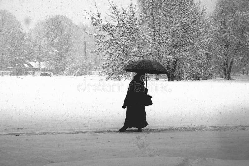 Mulher em uma tempestade de neve Silhueta fotos de stock royalty free