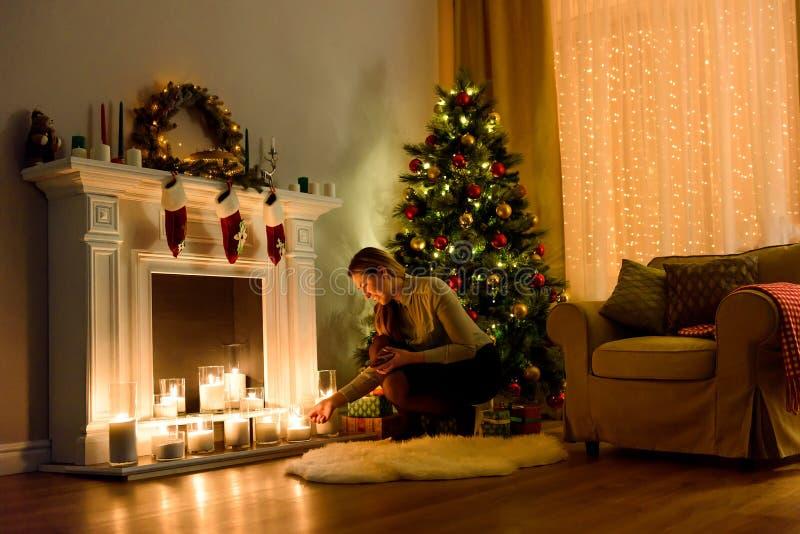 Mulher em velas de fixação iluminadas de uma sala do Natal foto de stock