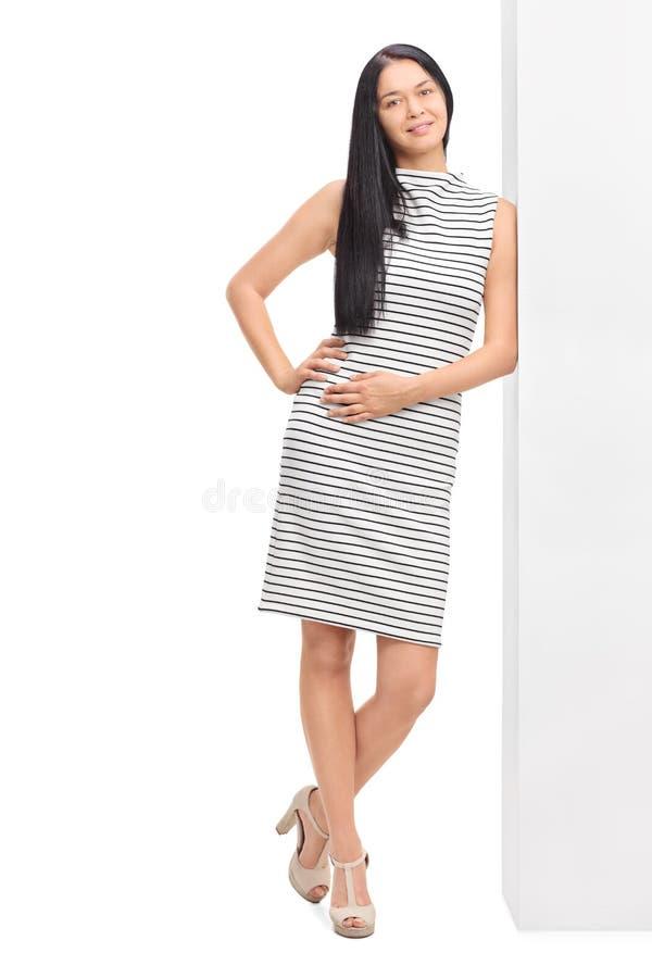 Mulher em vestido listrado que inclina-se contra uma parede fotos de stock