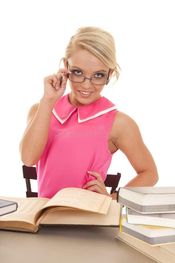A mulher em vidros dos livros da camisa do rosa quente guarda foto de stock royalty free