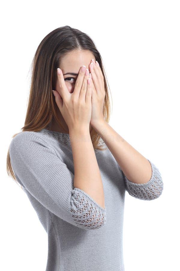 Mulher embaraçado que olha através de suas mãos que cobrem sua cara imagem de stock