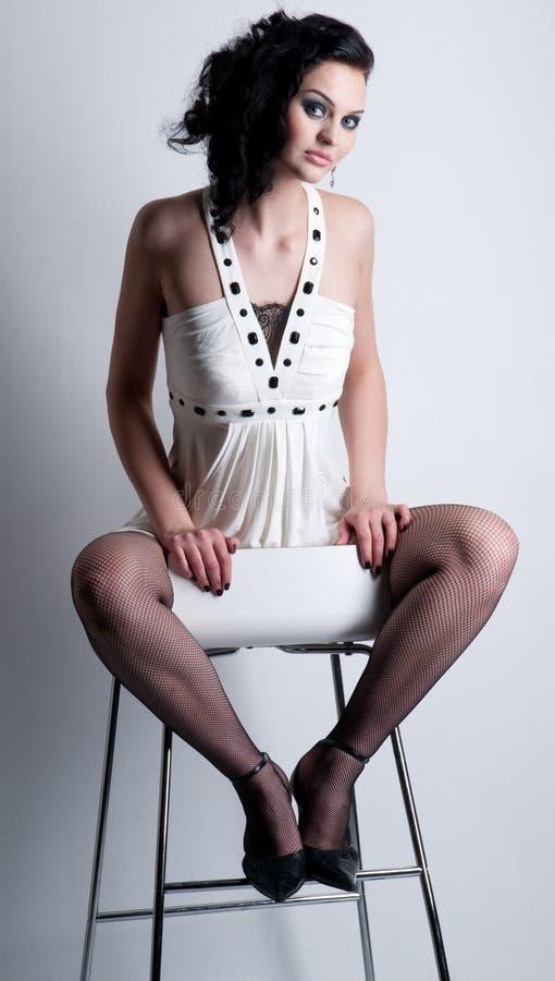 Mulher emocional bonita do encanto na cadeira. Moda foto de stock royalty free