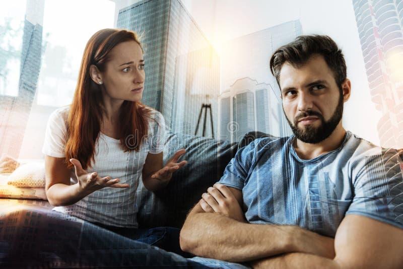 Mulher emocional que usa gestos ao falar a seu noivo indiferente foto de stock