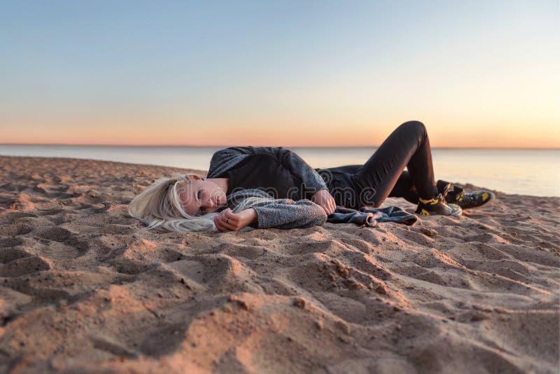 A mulher emocionalmente de sofrimento desagradável sombrio da menina encontra-se girando na areia na praia no por do sol foto de stock royalty free