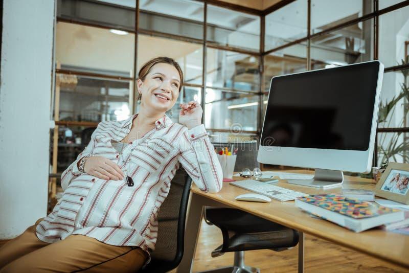 Mulher empregada grávida de olhos escuros que sente muito positiva fotografia de stock royalty free