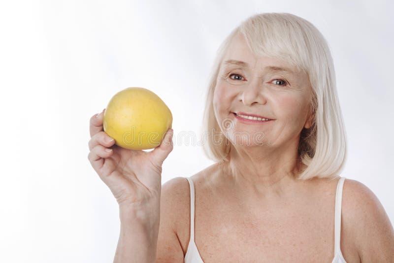 Mulher encantador agradável que guarda uma maçã fotos de stock royalty free