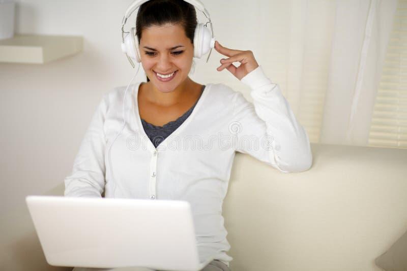 Mulher encantador com música de escuta do auscultadores fotografia de stock
