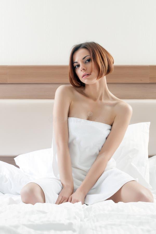 Mulher encantador com o cabelo curto que levanta após o chuveiro