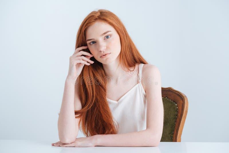 Mulher encantador do ruivo que senta-se na tabela foto de stock
