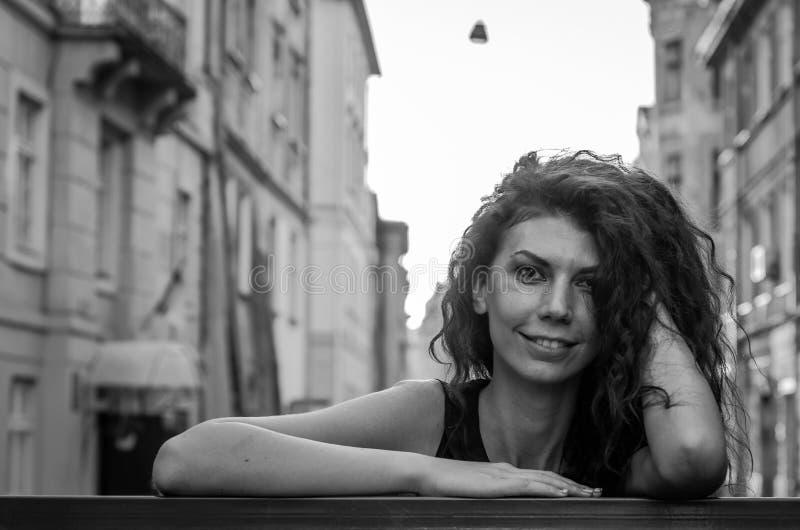Mulher encantador nova com o cabelo encaracolado longo, dando uma volta entre a cidade velha da arquitetura de Lviv no vestido pr fotos de stock royalty free