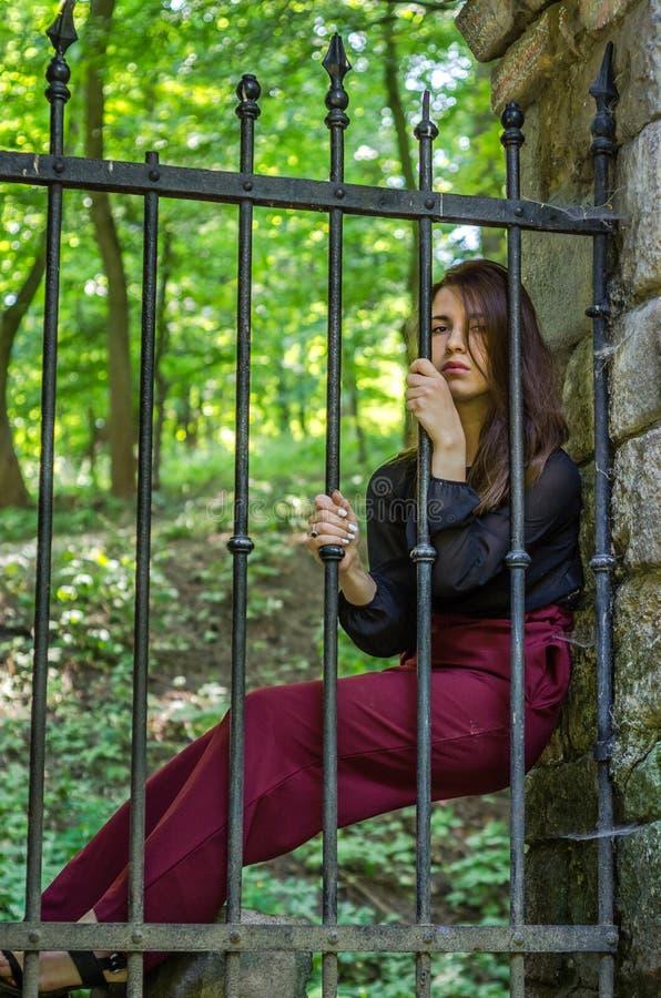 A mulher encantador nova com o delinquente longo do cabelo, senta-se atrás das barras em um prisioneiro de pedra antigo da prisão fotografia de stock royalty free